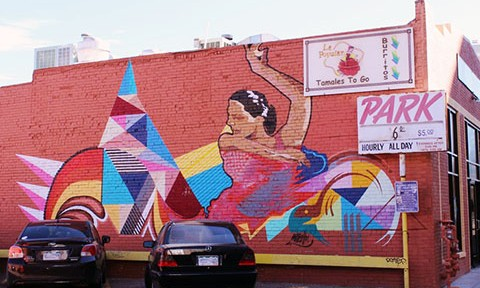 Colorful mural of woman dancing painted onto a brick wall of an older Denver establishment.